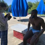 Giles Smith, a Fitter and Faster elite clinician speaks with a participant at a swim camp in Potomac, Maryland as she takes notes